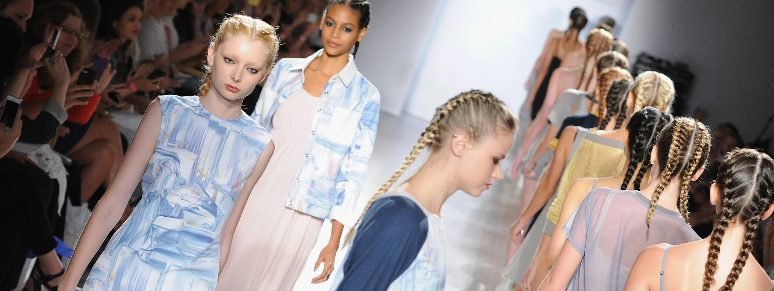 A number of models all with braided hairstyles walking down a catwalk