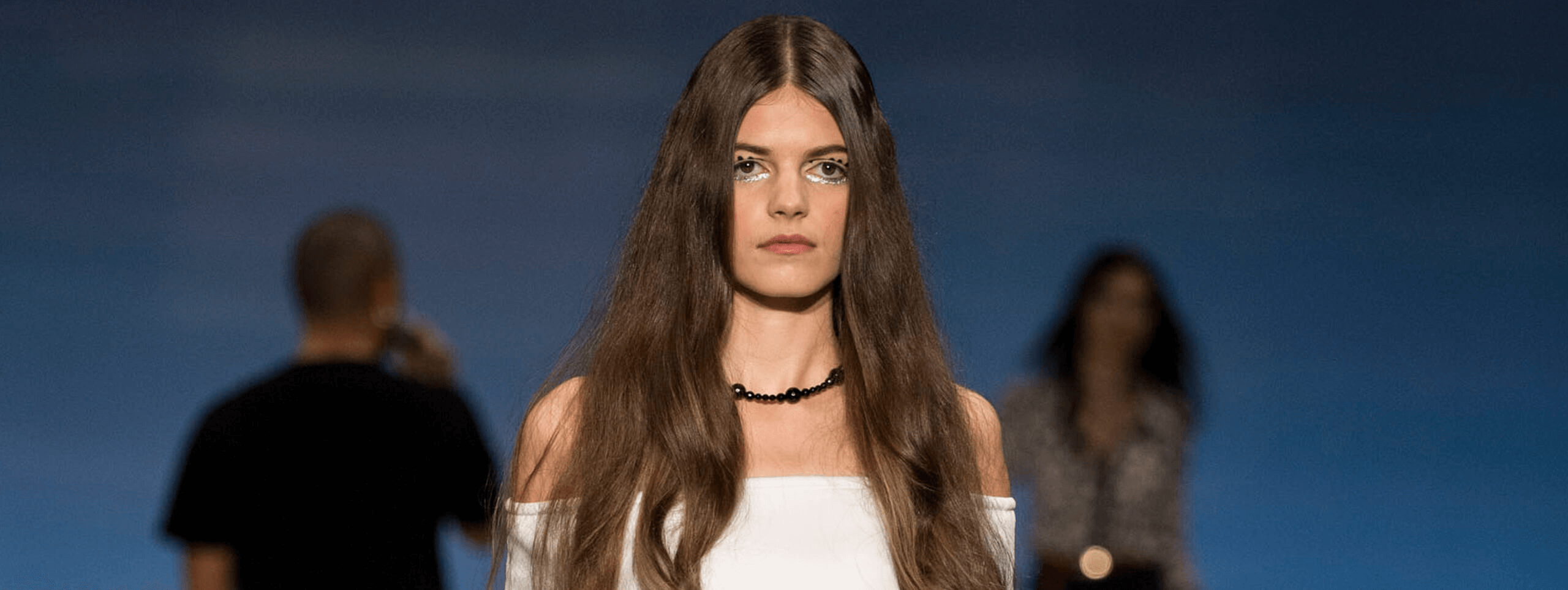 Model showcases middle parting hairstyle for dark brown hair