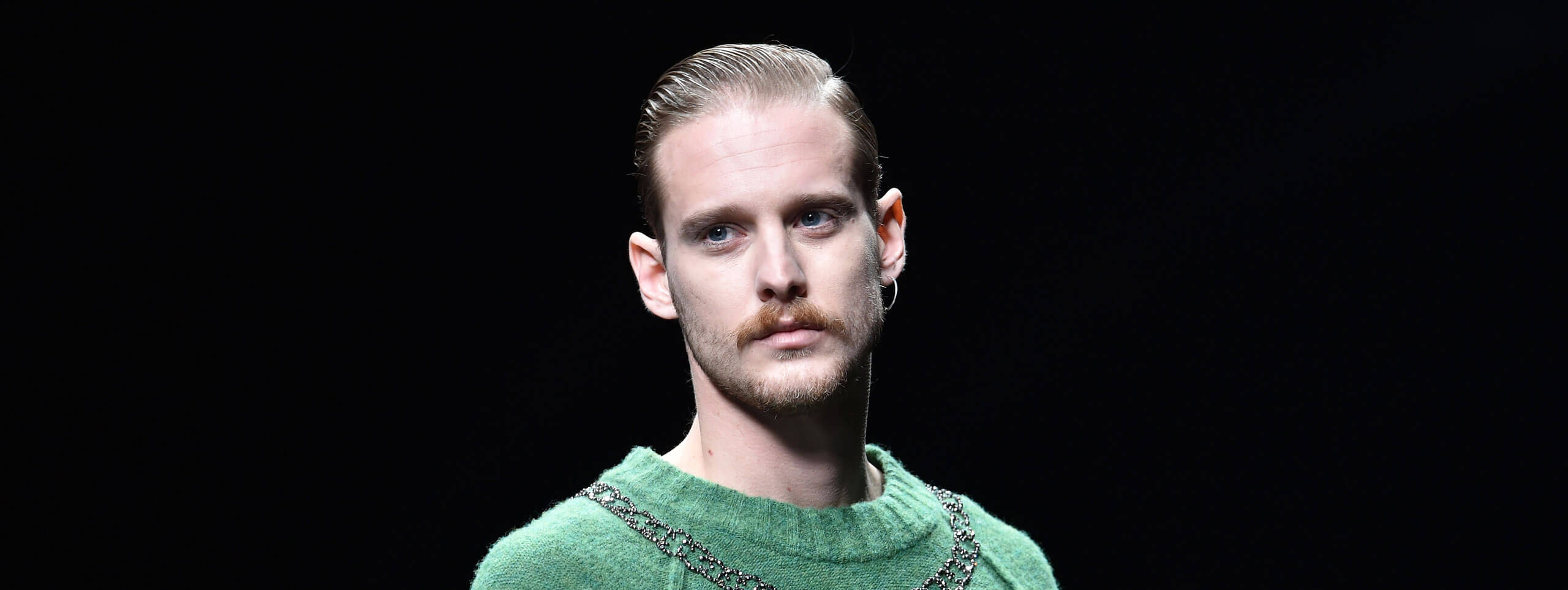 Male model with swept back hairstyle and an earring