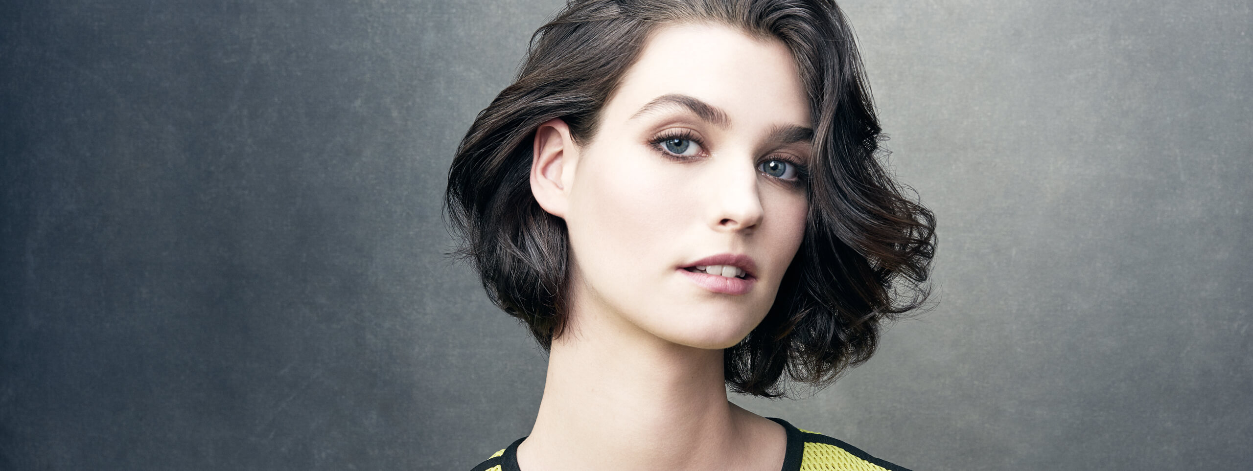 Model with hair swept back in a bob hairstyle