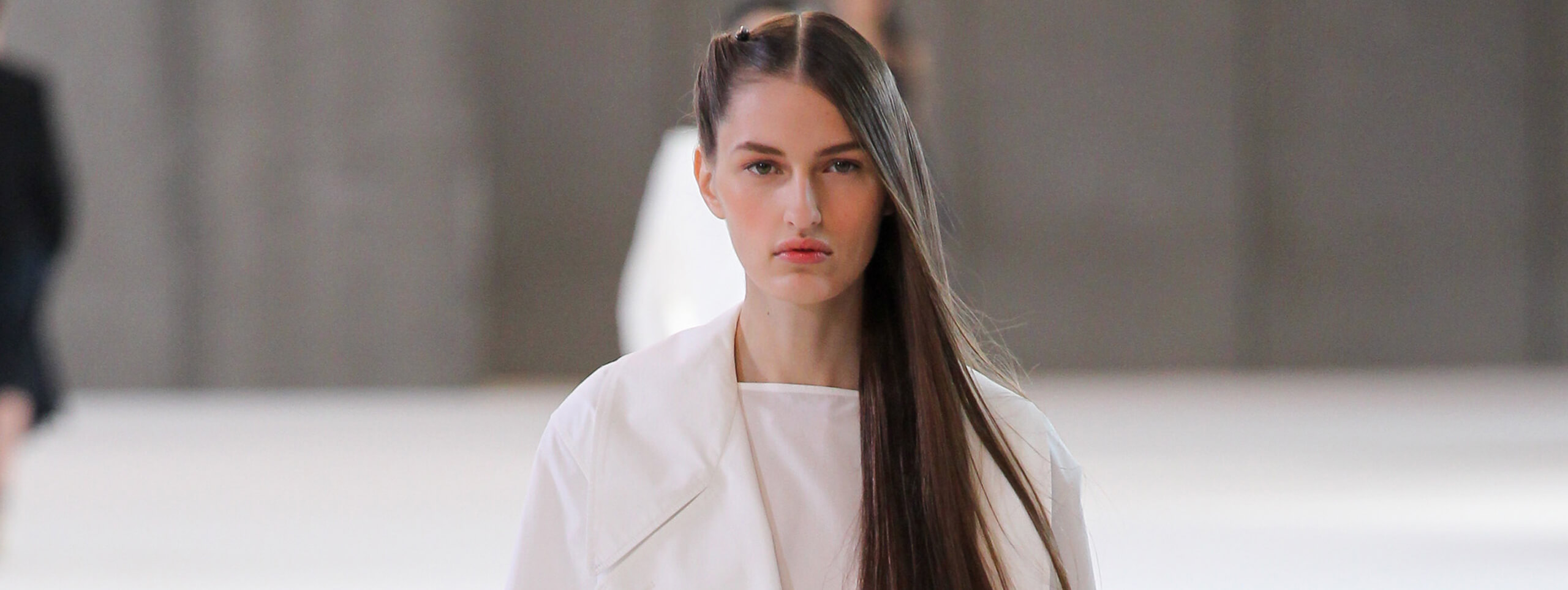 Model with long sleek hairstyle braided on one side