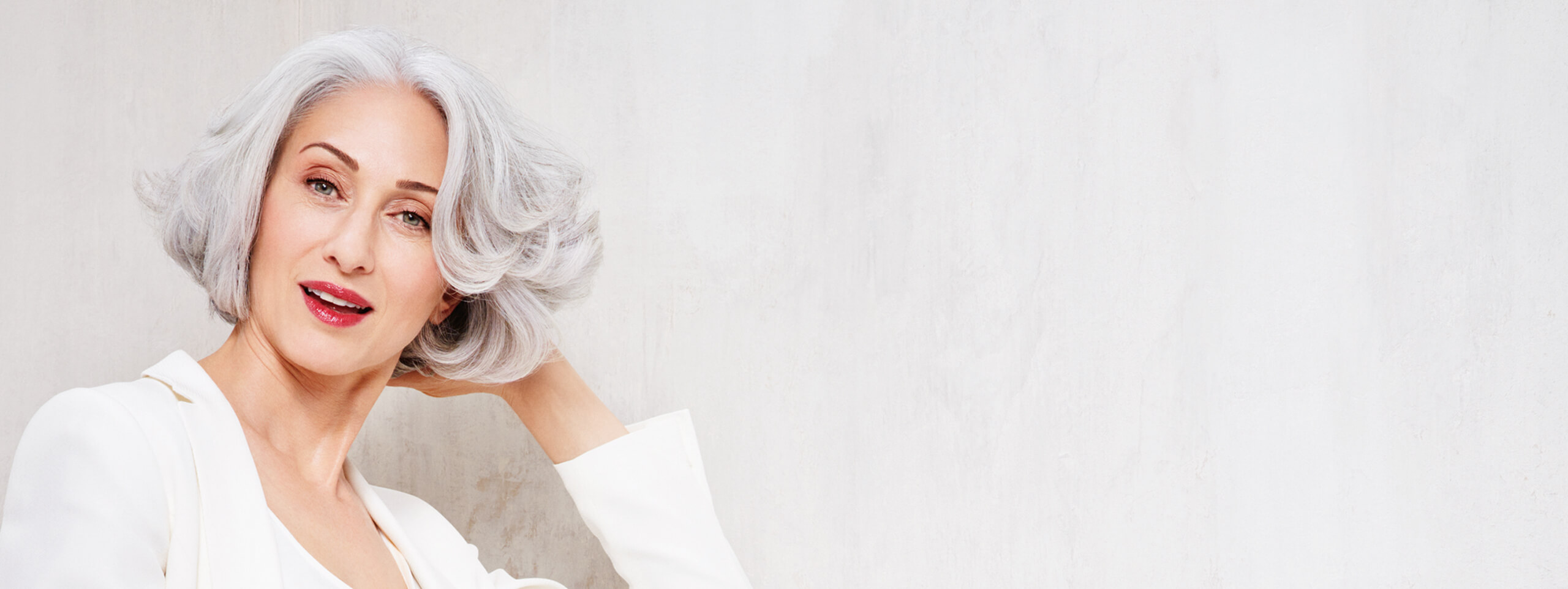 Woman wears light gray hair in a wavy bob hairstyle